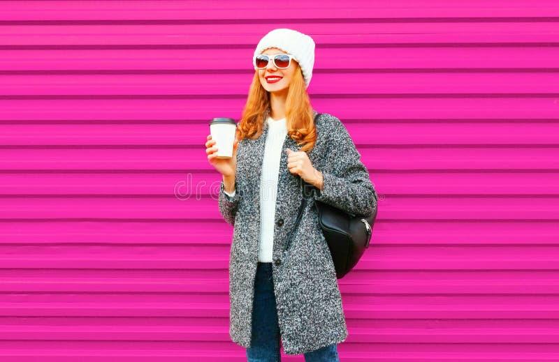 Mujer sonriente feliz con la taza de café caliente que lleva la capa gris fotos de archivo libres de regalías