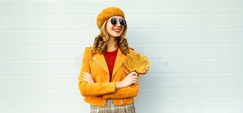 Mujer sonriente feliz con las hojas de arce amarillas que miran lejos en la calle de la ciudad sobre la pared gris foto de archivo