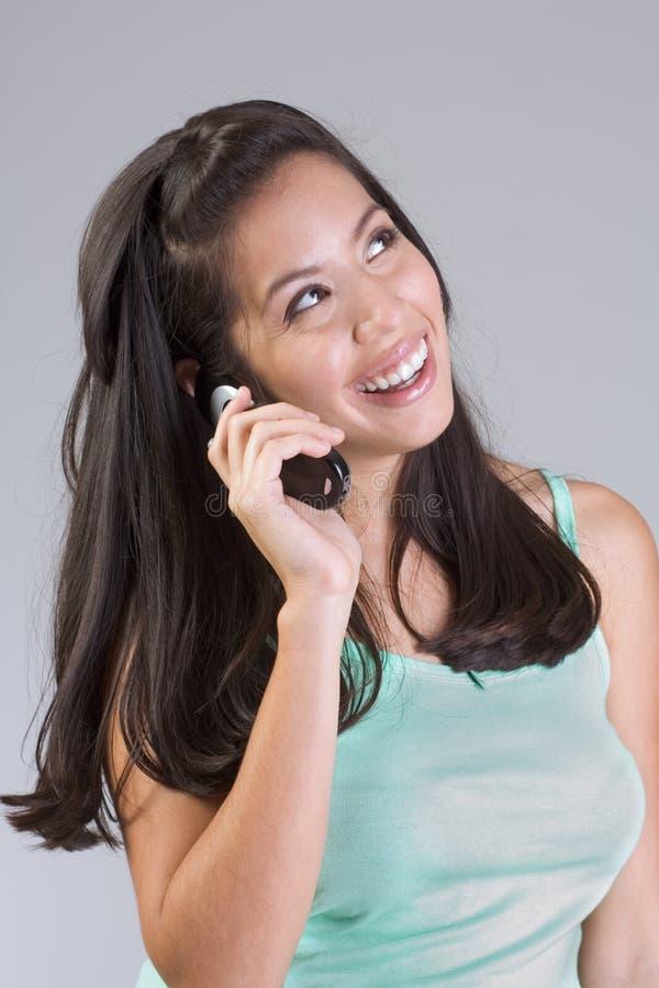 Mujer sonriente feliz de Latina que habla en el teléfono celular imagen de archivo libre de regalías
