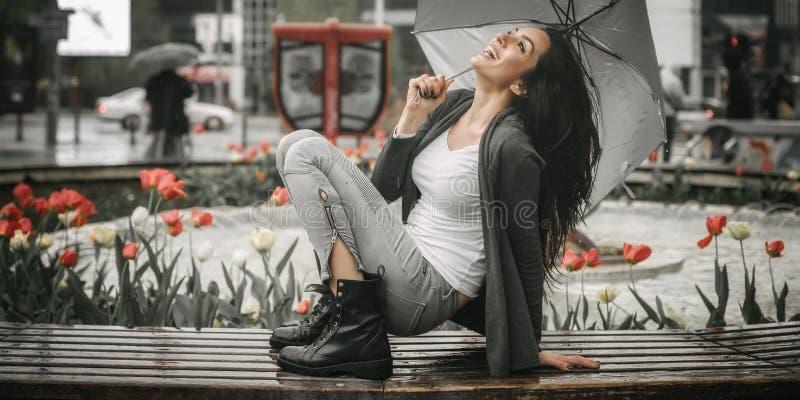 Mujer sonriente feliz debajo del paraguas en lluvia foto de archivo libre de regalías