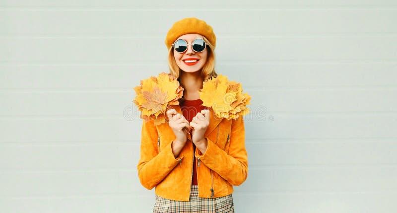 Mujer sonriente feliz del retrato del otoño con las hojas de arce amarillas en la calle de la ciudad sobre la pared gris fotos de archivo libres de regalías