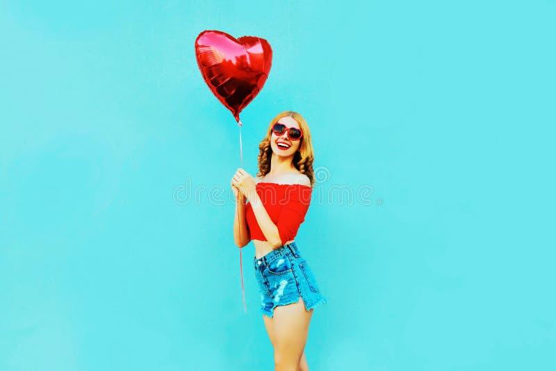 Mujer sonriente feliz del retrato que sostiene el balón de aire en forma de corazón rojo en azul colorido imagen de archivo libre de regalías