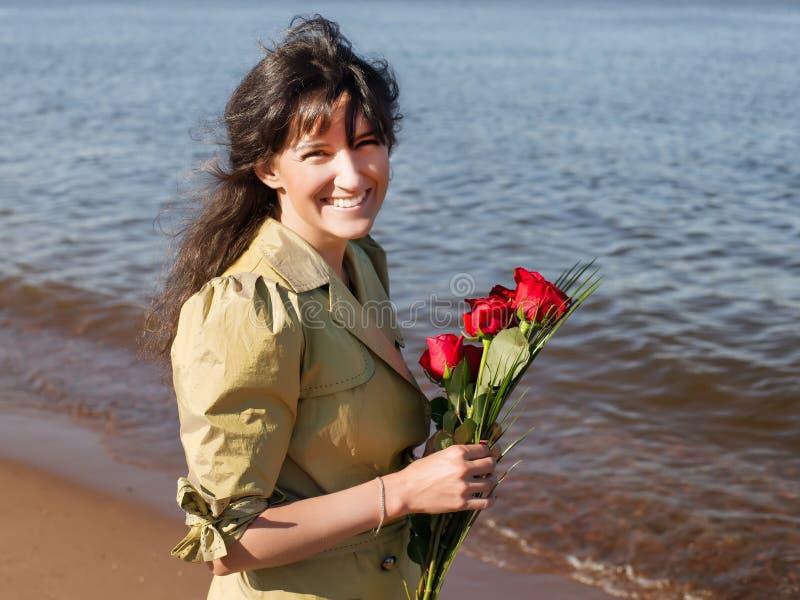 Mujer sonriente feliz en capa verde con el ramo de las rosas que bizquea a imágenes de archivo libres de regalías