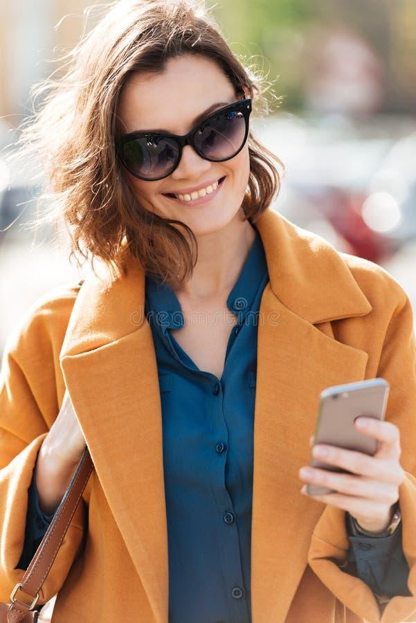 Mujer sonriente feliz en gafas de sol y capa foto de archivo libre de regalías