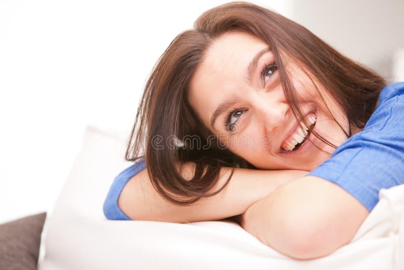 Mujer sonriente feliz en su sala de estar blanca foto de archivo
