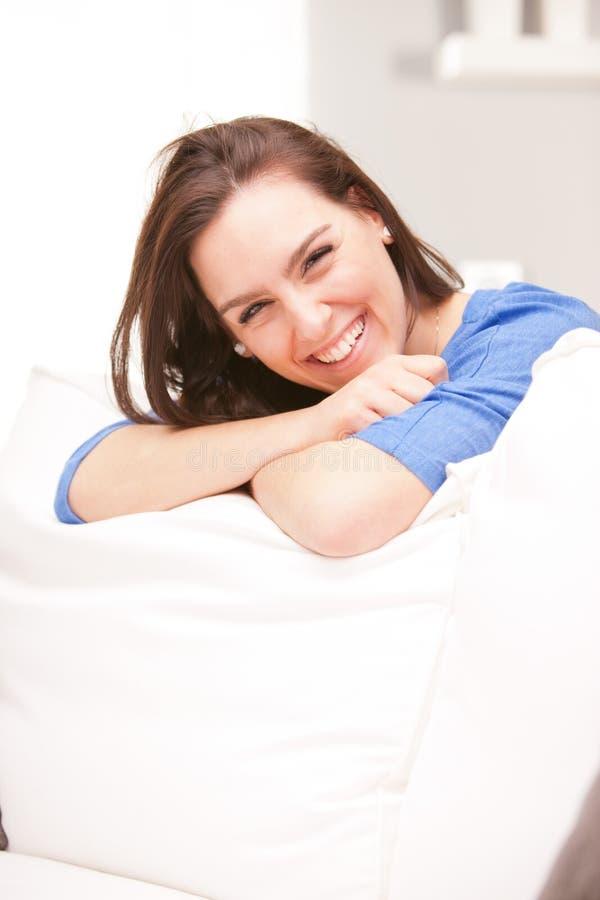 Mujer sonriente feliz en su sala de estar blanca fotografía de archivo libre de regalías