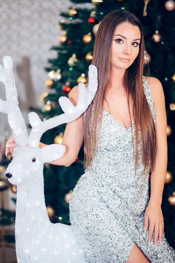 Mujer sonriente feliz en vestido que sorprende que celebra el partido del Año Nuevo, presentando cerca de un árbol de navidad imágenes de archivo libres de regalías