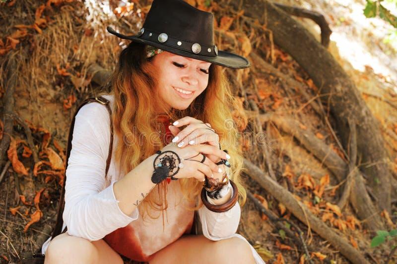 Mujer sonriente feliz hermosa con las pulseras elegantes y el sombrero de cuero negro, manicura blanca del dreamcatcher del boho fotos de archivo libres de regalías
