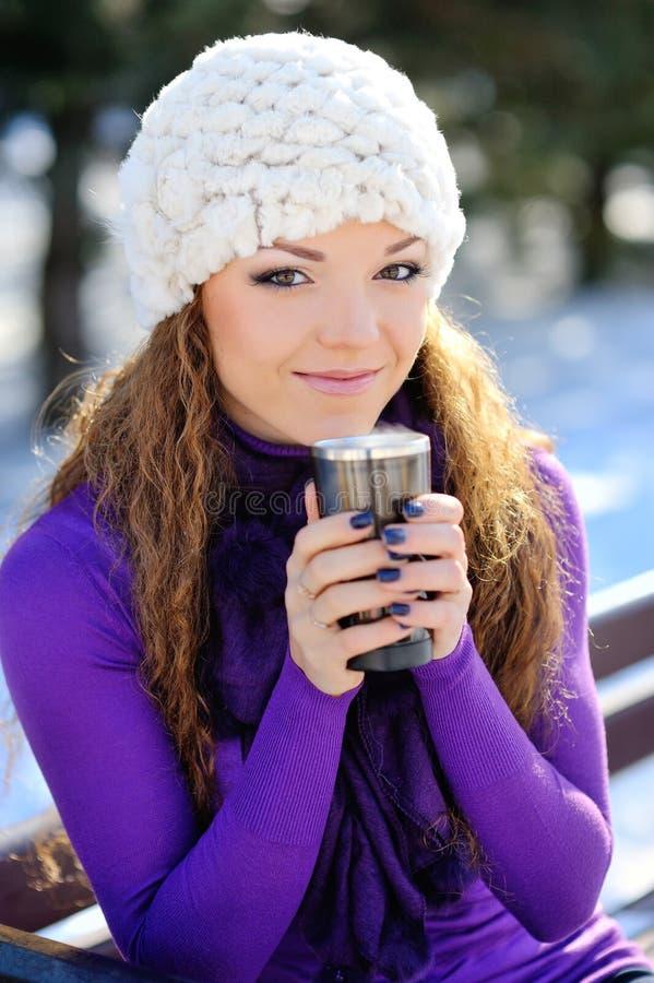 Mujer sonriente feliz hermosa del invierno con la taza al aire libre imagenes de archivo