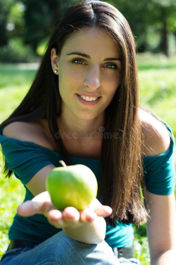 Mujer sonriente feliz joven con la manzana fotografía de archivo