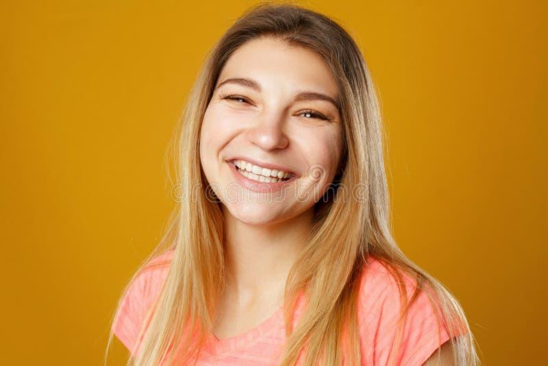 Mujer sonriente feliz joven hermosa que presenta en estudio sobre amarillo imagenes de archivo