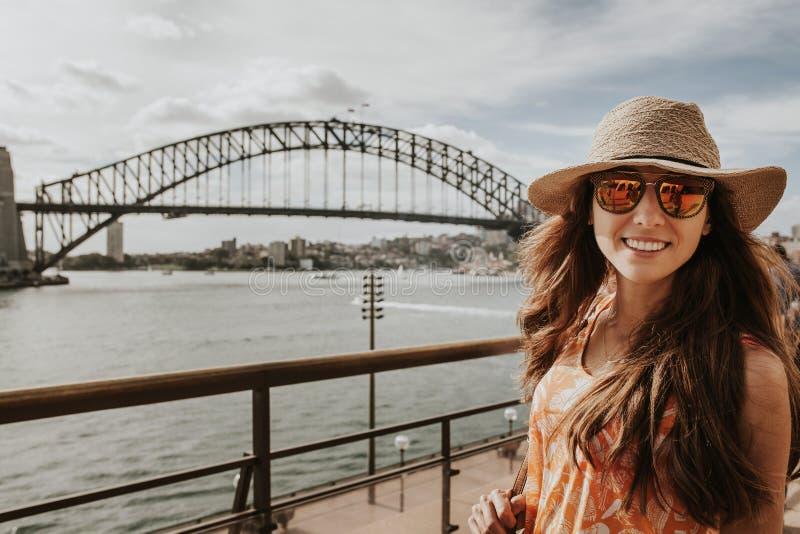 Mujer sonriente feliz que explora Sydney, con el puente del puerto en el fondo fotos de archivo