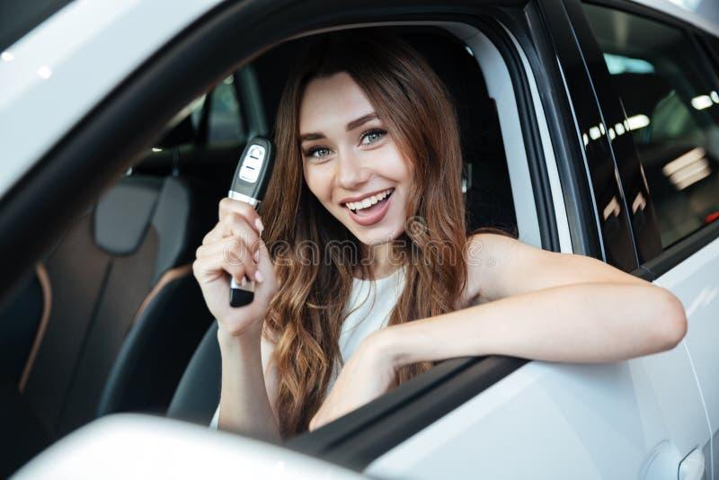 Mujer sonriente feliz que se sienta dentro de su nuevo coche foto de archivo libre de regalías