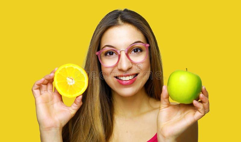 Mujer sonriente feliz que sostiene la media manzana anaranjada y verde en un fondo amarillo imagenes de archivo