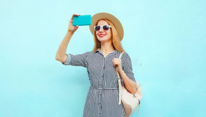 Mujer sonriente feliz que toma la imagen del selfie por el teléfono en el sombrero de paja de la ronda del verano, vestido rayado fotografía de archivo libre de regalías