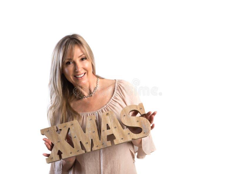 Mujer sonriente festiva que lleva a cabo palabra de Navidad en el fondo blanco Chr foto de archivo