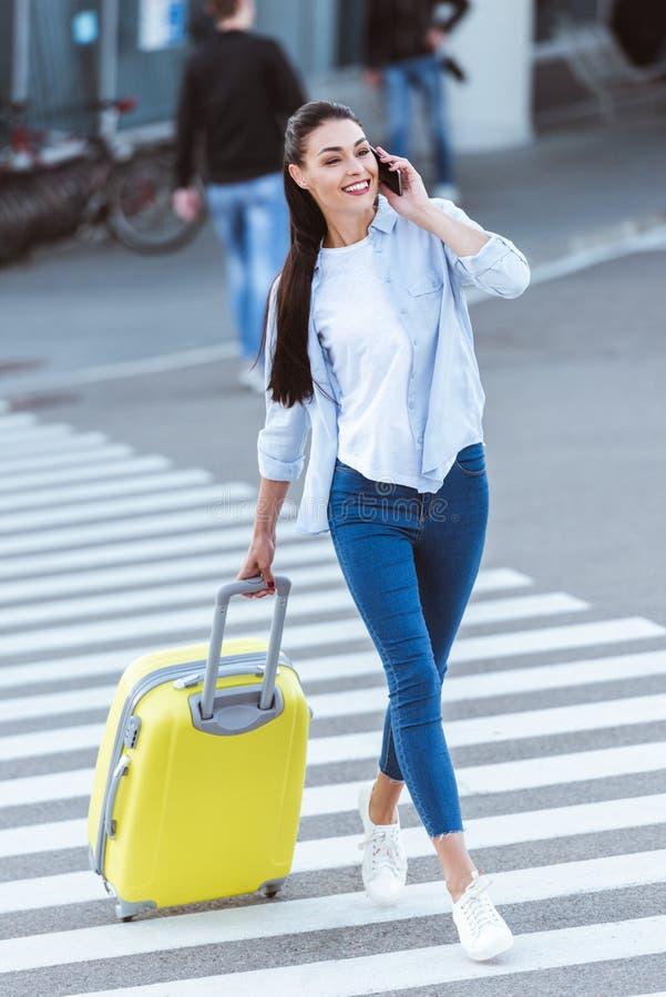 Mujer sonriente hermosa con el peatón que cruza y hablar del bolso amarillo del viaje imagen de archivo libre de regalías