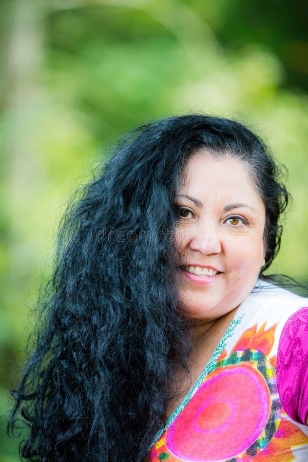 Mujer sonriente hermosa con el pelo negro largo que lleva una blusa blanca con los modelos coloridos fotos de archivo libres de regalías