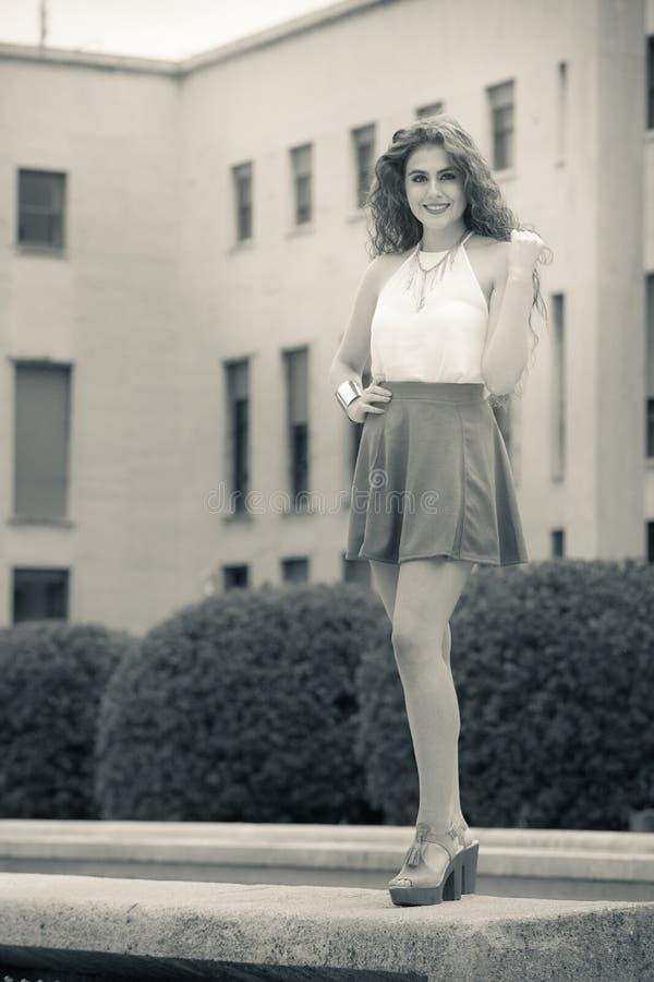 Mujer sonriente hermosa con el pelo rizado Mirada elegante urbana imagen de archivo