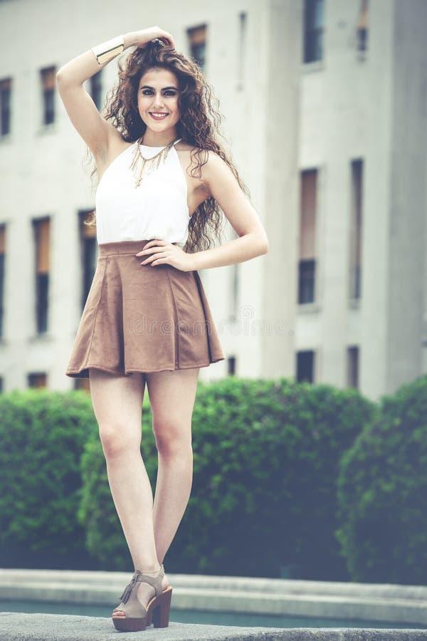 Mujer sonriente hermosa con el pelo rizado Mirada elegante urbana imagen de archivo libre de regalías