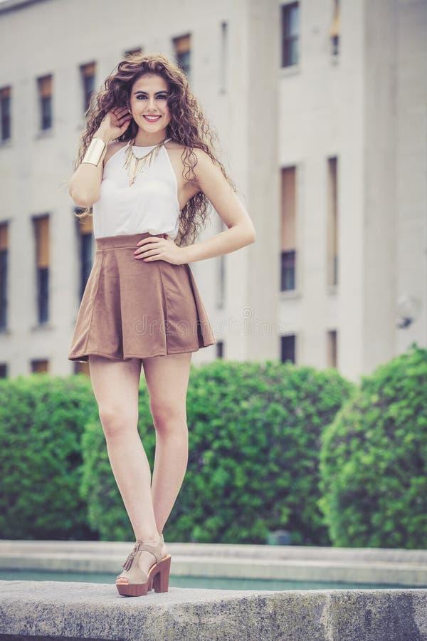 Mujer sonriente hermosa con el pelo rizado Mirada elegante urbana fotografía de archivo