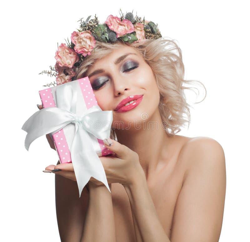 Mujer sonriente hermosa con el regalo rosado Mujer alegre feliz con el pelo rubio, el maquillaje y las flores aislados en el fond imagen de archivo