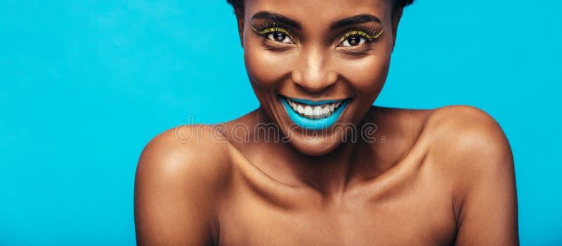 Mujer sonriente hermosa con maquillaje vibrante imagen de archivo libre de regalías