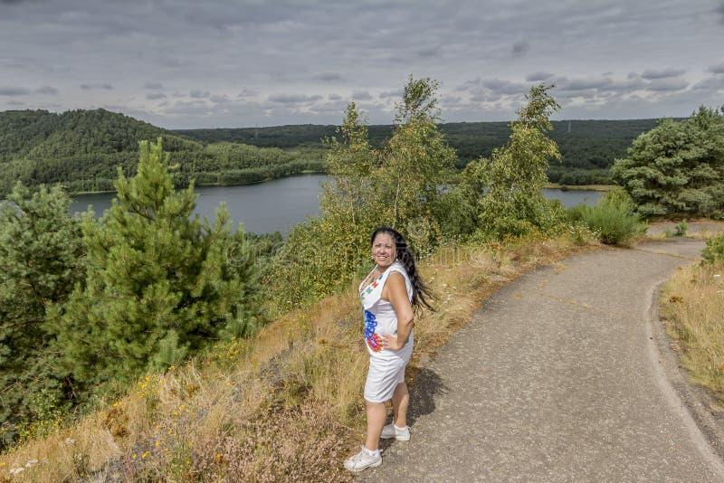 Mujer sonriente hermosa con ropa blanca que lleva larga del pelo negro en una colina con una trayectoria y un lago en el fondo fotografía de archivo