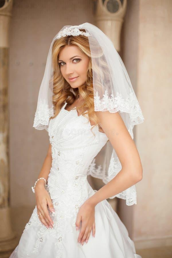Mujer sonriente hermosa de la novia en el vestido de boda y el velo nupcial p fotos de archivo libres de regalías