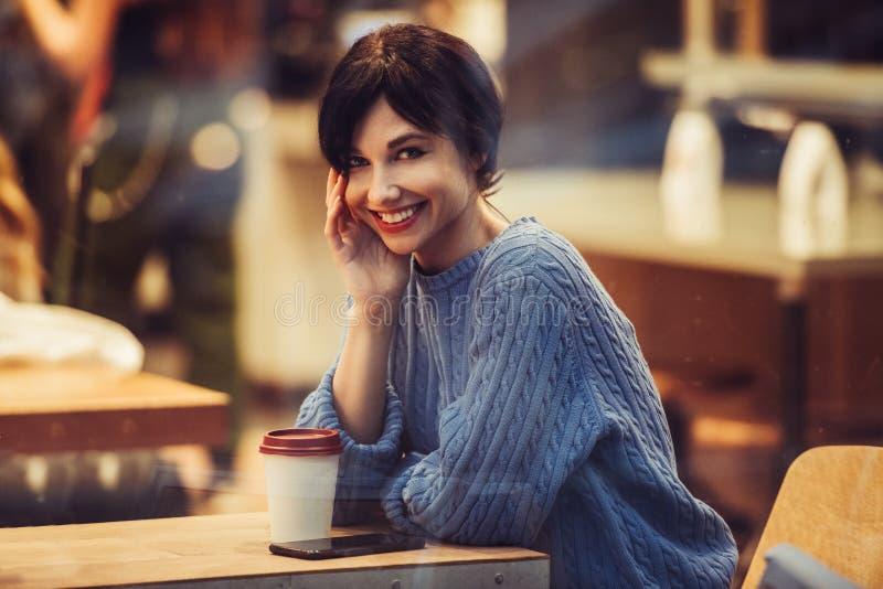 Mujer sonriente hermosa en el café con café interior y de consumición acogedor caliente fotos de archivo libres de regalías