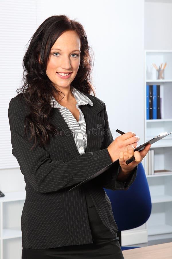Mujer sonriente hermosa en el trabajo con el sujetapapeles fotos de archivo libres de regalías