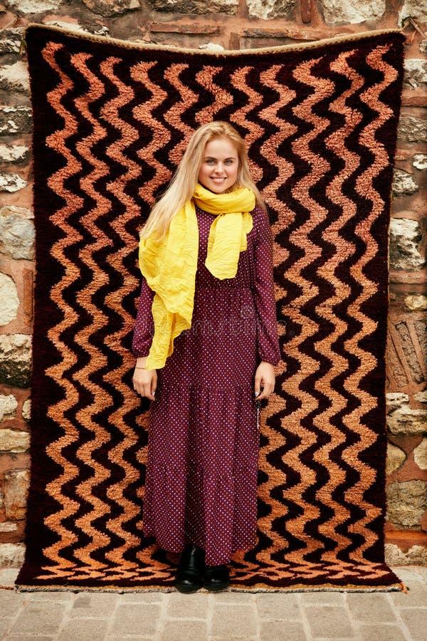 Mujer sonriente hermosa en vestido y bufanda con la alfombra turca imagen de archivo libre de regalías