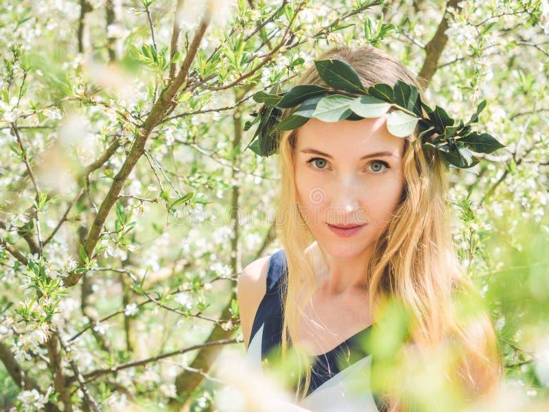 Mujer sonriente hermosa joven en árboles del flor de la primavera imagenes de archivo