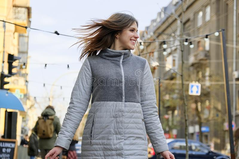 Mujer sonriente hermosa joven que camina a lo largo de la calle de la ciudad de la primavera imagen de archivo