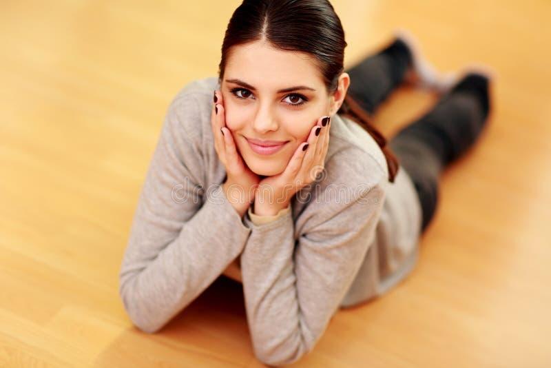Mujer sonriente hermosa joven que miente en el piso imagen de archivo