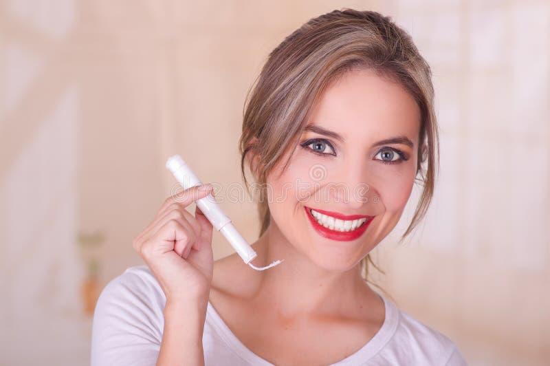 Mujer sonriente hermosa joven que sostiene un tapón del algodón de la menstruación en su mano, en un fondo borroso imágenes de archivo libres de regalías