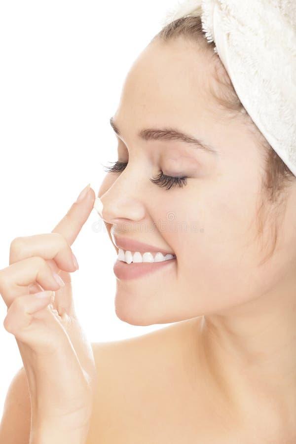 Mujer sonriente hermosa que aplica la crema de la crema hidratante foto de archivo libre de regalías