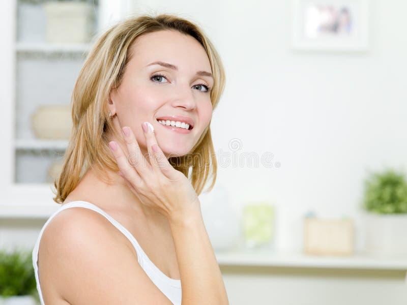 Mujer sonriente hermosa que aplica la crema en cara imagen de archivo libre de regalías