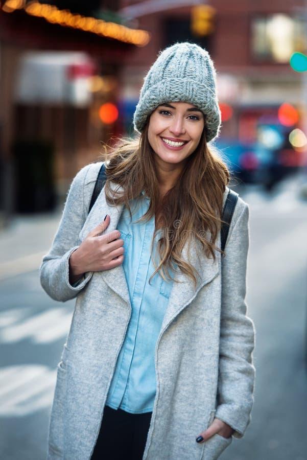 Mujer sonriente hermosa que camina en la calle de New York City que lleva la ropa casual fotografía de archivo