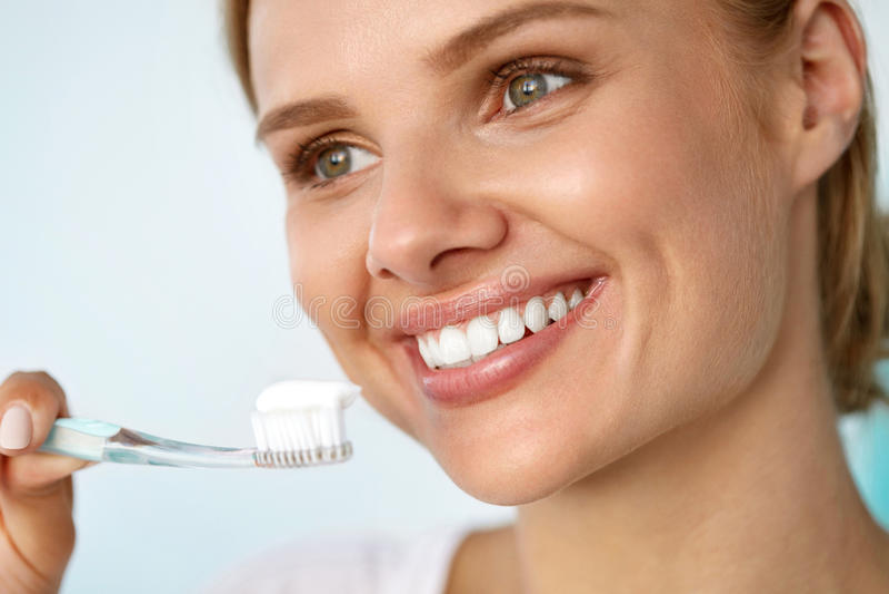 Mujer sonriente hermosa que cepilla los dientes blancos sanos con el cepillo foto de archivo libre de regalías
