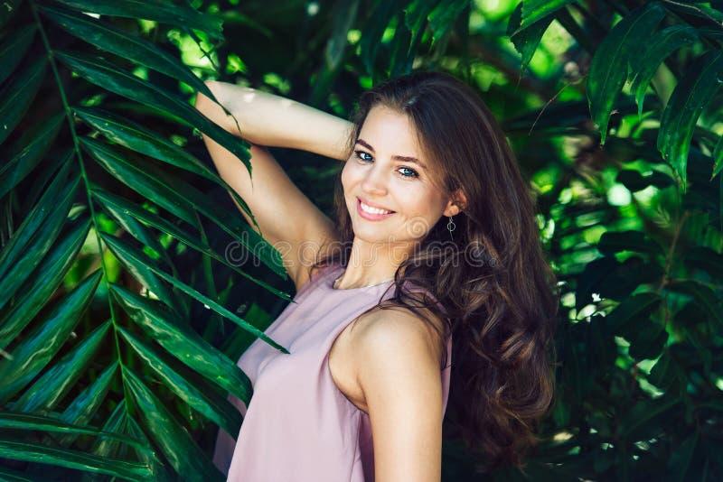 Mujer sonriente hermosa que presenta en fondo tropical verde natural del bosque foto de archivo libre de regalías