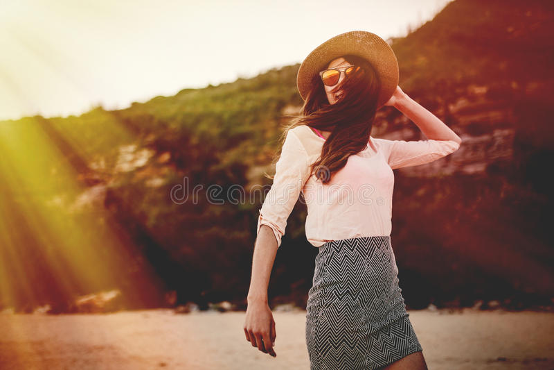 Mujer sonriente hermosa que presenta en la naturaleza con gafas de sol y un sombrero imagen de archivo libre de regalías
