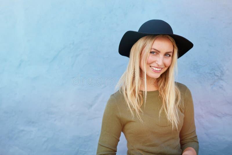 Mujer sonriente hermosa que presenta por la pared azul fotografía de archivo