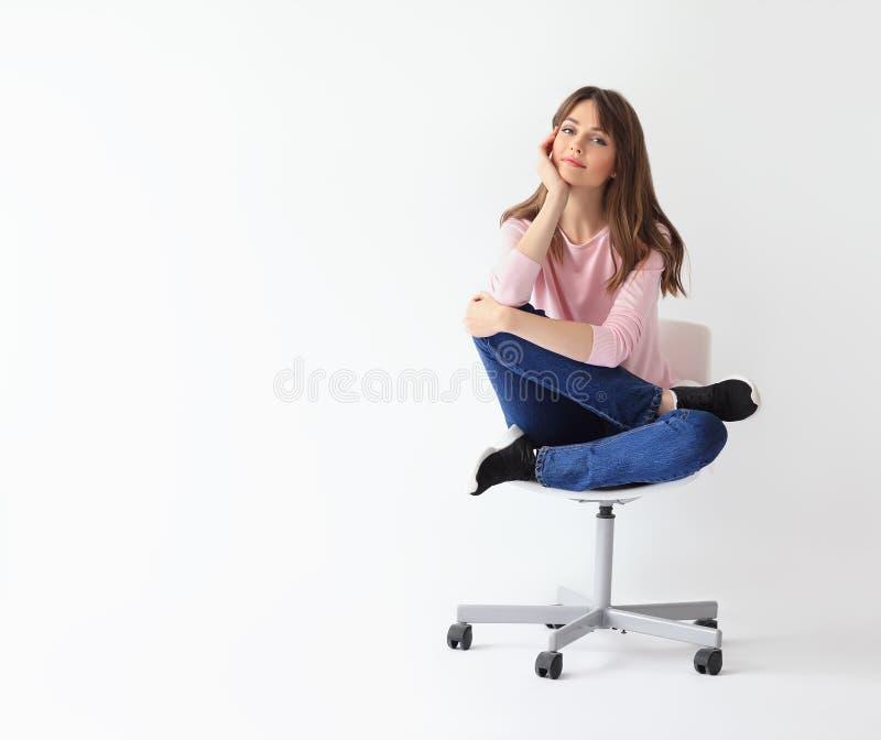 Mujer sonriente hermosa que se sienta en silla con el espacio de la copia fotos de archivo libres de regalías