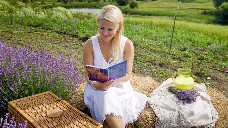 Mujer sonriente hermosa que tiene comida campestre en libro del campo y de lectura fotos de archivo