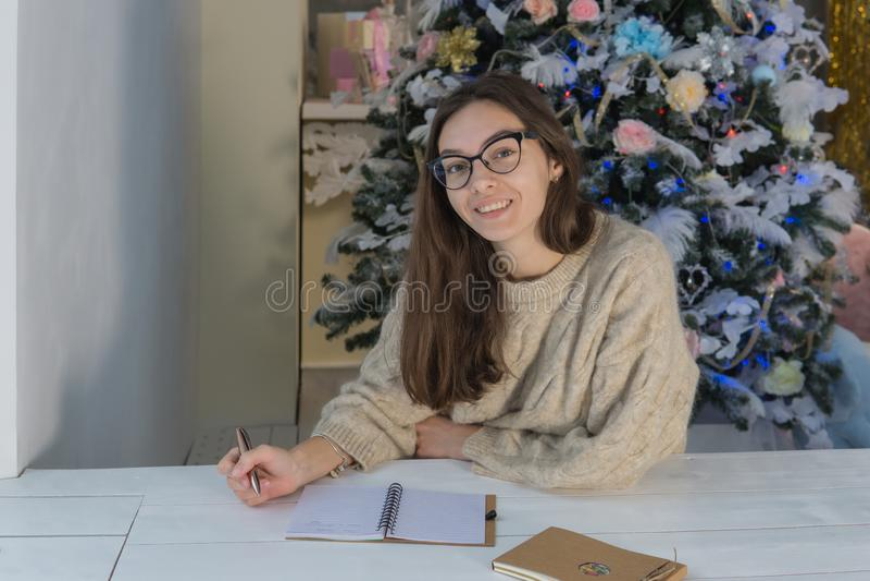 Mujer sonriente joven al lado del árbol que mira la cámara y la sonrisa foto de archivo libre de regalías