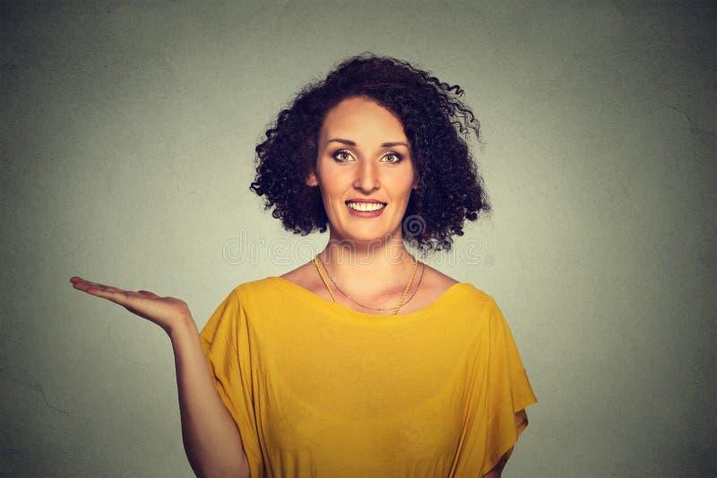 Mujer sonriente joven bastante confiada feliz que gesticula presentando el espacio en la izquierda foto de archivo libre de regalías