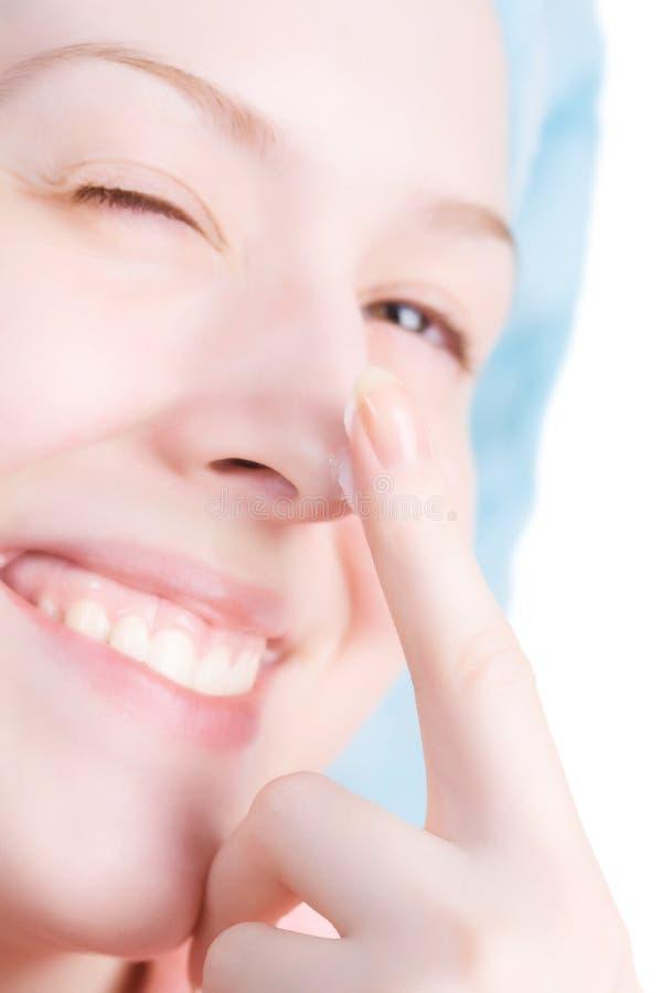 Mujer sonriente joven con crema en nariz fotos de archivo