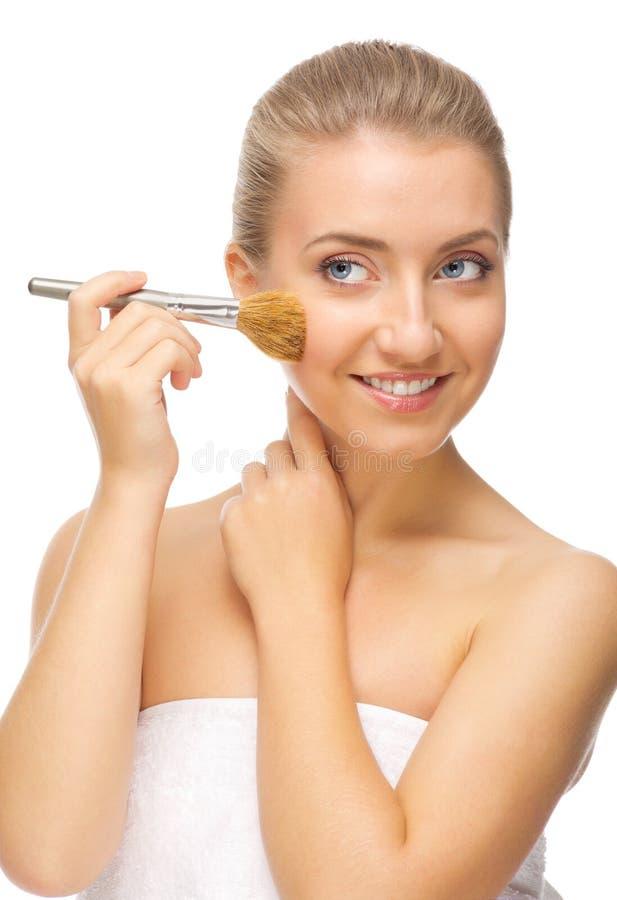 Mujer sonriente joven con el cepillo del maquillaje imagen de archivo libre de regalías