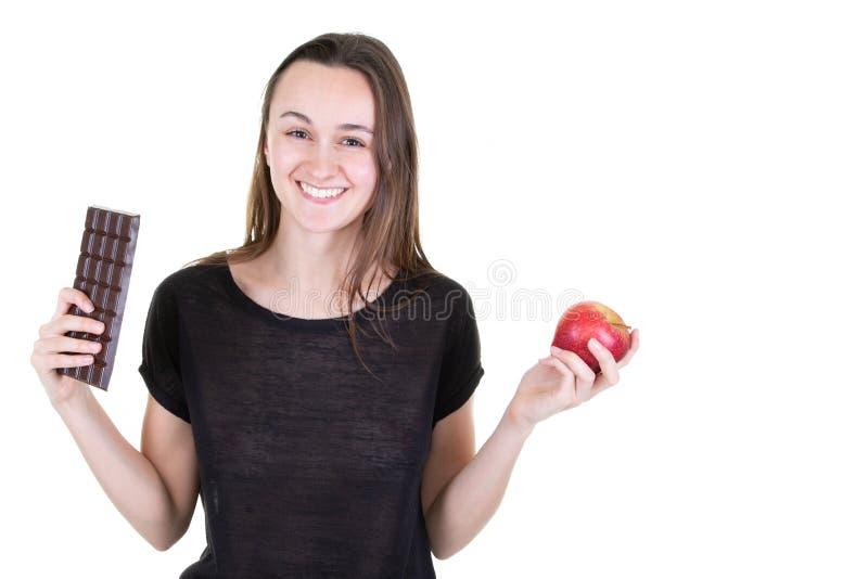 Mujer sonriente joven con el chocolat y una manzana que tiene dudas fotos de archivo libres de regalías